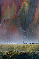 Fine art nature abstract of geyser, showing 2 layers of base rings of travertine mound on which geyser sits and continues to grow, with layers being pummeled by showers of water spray and water drops coming from top of geyser not shown in image, with brilliant reds, oranges, yellows and greens caused by thermophilic algae flourishing under varying temperatures of hot, geothermal water.