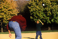 Dad pitches a wiffle ball to his son in the park.