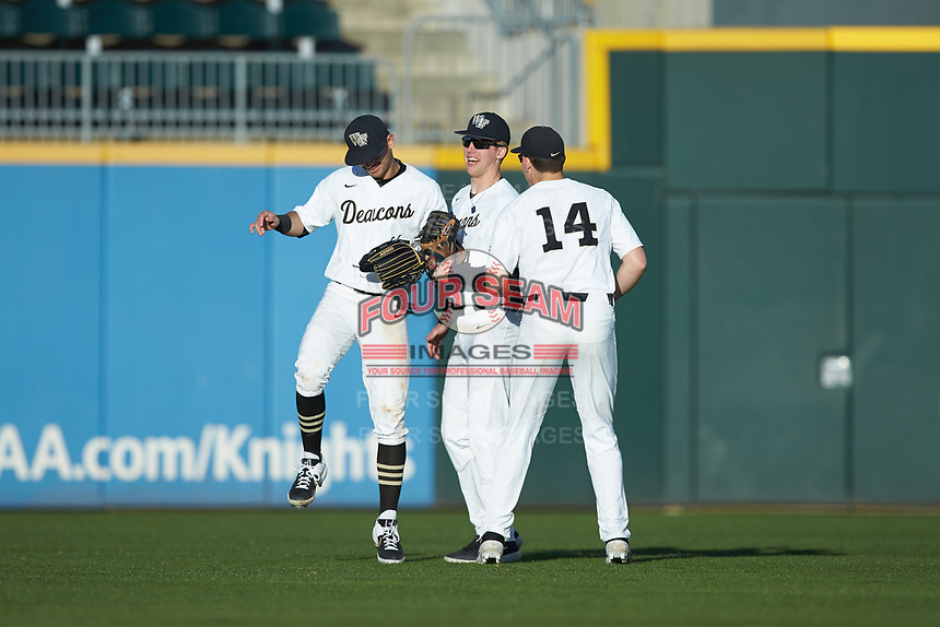 (L-R) Patrick Frick (5), DJ Poteet (4), and Drew Kendall (14) celebrate following the win over the Furman Paladins at BB&T BallPark on March 2, 2019 in Charlotte, North Carolina. The Demon Deacons defeated the Paladins 13-7. (Brian Westerholt/Four Seam Images)