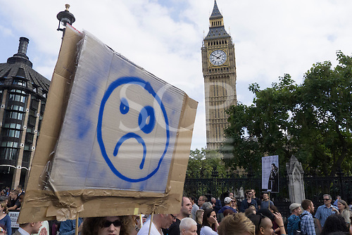 A protester holds a cardboard placard with a grumpy face and a black eye as she passes the tower of Big Ben during the Climate Change demonstration, London, 21st September 2014. © Sue Cunningham
