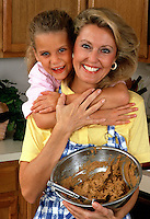 A smiling mother and young daughter mixing cookie dough in the the kitchen.