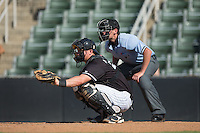Kannapolis Intimidators catcher Nate Nolan (24) frames a pitch as home plate umpire Anthony Perez looks on during the game against the Greensboro Grasshoppers at Intimidators Stadium on July 17, 2016 in Greensboro, North Carolina.  The Intimidators defeated the Grasshoppers 3-2 in game one of a double-header.  (Brian Westerholt/Four Seam Images)
