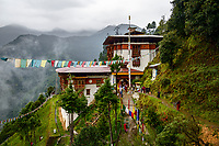 Tango Goemba (Cheri Goemba), an impressive Buddhist monastery located high on a steep mountainside overlooking the mist and rain-clad Himalaya foothills. Buddhist monks go about their daily work in the grounds of the monastery.