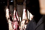 A shop owner sells raw lamb and beef meat while it hangs against the back wall of a small hut at a market on the outskirts of Arusha, Tanzania on September 24, 2008.  Due to lack of electricity meat is rarely ever refridgerated in Tanzania and East Africa and because of this much of the population lives in close contact with livestock, leaving them suspetible to many health concerns including some neglected tropical diseases such as fascioliasis.