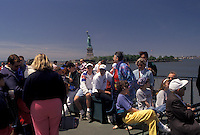 AJ4344, Statue of Liberty, tourboat, New York City, Manhattan, N.Y.C., New York, NYC, Tourists aboard the Statue of Liberty Ferry on a sunny day leaving Battery Park in Lower Manhattan in New York City in the state of New York. Statue of Liberty can be seen in the distance.