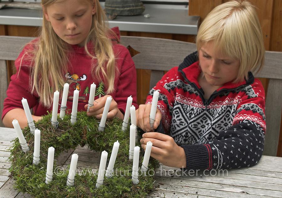 Kinder basteln einen Lichterkranz für die Adventszeit, Adventskranz, Kinder stecken Kerzen mit Draht in den Kranz, Lichterkranz mit 24 brennenden Kerzen für den 1. bis 24. Dezember