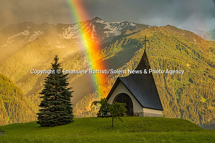 "Pictured: A magnificent rainbow stretches across the sky as it appears to emerge from a quaint chapel in the Austrian hills. <br /> <br /> The natural phenomenon was captured by mechanical engineer Emanuele Battisti as he was travelling through the countryside with his wife. <br /> <br /> The vivid colours of a single rainbow illuminate the overcast sky as the Chapel Krebsbach can be found sitting at the end of the rainbow in Barwies, Austria - only for another to appear moments later. <br /> <br /> The 43 year-old said ""I was travelling with my wife when i saw this magnificent opportunity passing us. I told my wife to get in the drivers seat so we could park and I could take some photographs"" <br /> <br /> Originally from Italy, Mr Battisti said ""These kinds of situations do not come along very often in the lifetime of a photographer: there is no way you can plan this type of photo and I usually don't have much luck!"" <br /> <br /> ""I was super excited because I was so lucky to be at the right time in the right place, with a magical light at the sunset.""<br /> <br /> Please byline: Emanuele Battisti/Solent News<br /> <br /> © Emanuele Battisti/Solent News & Photo Agency<br /> UK +44 (0) 2380 458800"