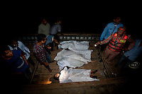 Bangladeshi rescue workers collect dead bodies of victims of the ferry capsized in the River Padma Sunday after being hit by a cargo vessel at Paturia, in Manikganj district, about 80 kilometers  northwest of Dhaka, Bangladesh. Feb. 22, 2015