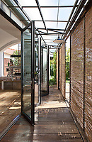 Modern glass doors open from the living area onto an exterior walkway shielded by a series of rattan blinds
