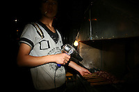 CHINA. Beijing. A man users a hairdryer to help him cook Chinese kebabs in the shopping district of Xinjiekou . 2008