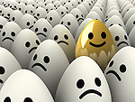 Full frame shot of one happy golden egg amongst sad while eggs representing profit and loss