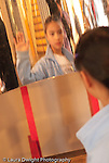 8 year old girl looking at self in distorted curved reflecting surface at the Exploratorium The Museum of Science,Art, and Human Perception in San Francisco CA USA vertical