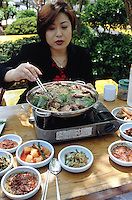"""Korea. South Korea. Incheon. 30 km from Seoul. A woman eats with her friends dog meat on a saturday lunch in a restaurant specialised with dog food.  """"Bosintang"""" dish has dog meat cooked in a soup with various spices (ginseng, soya,..) and vegetables. On the side lies diferents plates with pickles, carots, cabbages,...  Dog meat is a delicatessen of korean traditionnal cooking.  © 2002 Didier Ruef"""