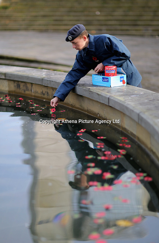 Pictured: A lone cadet deposits poppies in the fountain Friday 11 November 2016<br />Re: Remembrance Day service at Castle Square Gardens in Swansea, south Wales, UK.