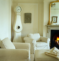 Corner of the off-white living room with a traditional Swedish-style grandfather clock