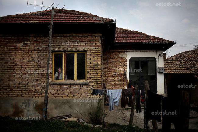 BULGARIA, Cherkovna, April 13, 2011. A Bulgarian muslim woman looks through the window of her house in the remote village of Cherkovna north of Bulgaria. Bulgarian Muslims, which today are nearly 8% of the country's population and the largest muslim minority community in the European Union, revived their cultural and religious traditions after the fall of communist regime in Bulgaria in 1989. .BULGARIE, Cherkovna, 13 Avril 2011. Une Bulgare de confession musulmane regarde par la fenêtre de sa maison dans le petit village de Cherkovna au nord de la Bulgarie. La minorité musulmane qui représente aujourd'hui près de 8% de la population totale du pays et qui est la plus large majorité musulmane dans les pays de l'Union Européenne a ravive ses traditions culturelles et religieuse après la chute du régime communiste Bulgare en 1989.