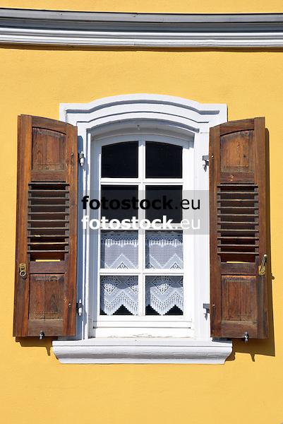 weißes Fenster mit braunen Fenterläden an gelber Fassade
