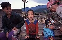 Laos, Luang Namtha Province, Ban Nammat Gao village, 12/3/03..Akha family together after work at the end of the afternoon. The young child is already wearing a traditional head-dress...Photo Kees Metselaar