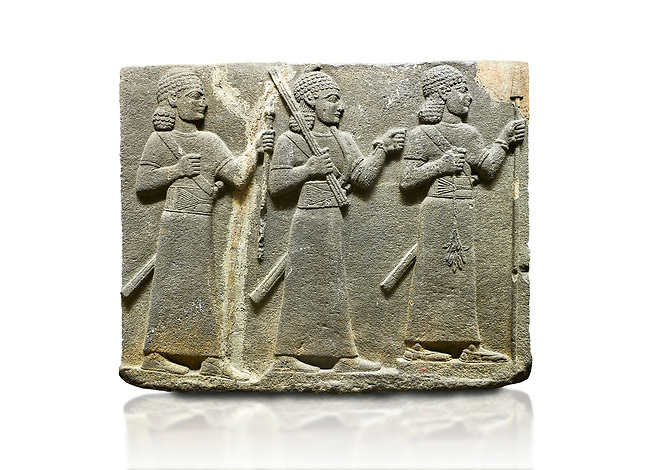 Hittite relief sculpted orthostat stone panel of Royal Buttress Basalt, Karkamıs, (Kargamıs), Carchemish (Karkemish), 900-700 B.C. Warriors. Anatolian Civilisations Museum, Ankara, Turkey.<br /> <br /> Three figures each with a long dress, a thick belt and curly hair. The figure in front holds a spear with a broken tip in his left hand and a leafy branch in his right hand. The figure in the middle made his left hand a fist, and he carries a tool with his right hand at the level of his head. They are followed with a figure holding a sceptre in his left hand. All three have each a long sword at their waist. <br /> <br /> Against a white background.