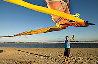 A young boy flies a giant kits on the beach. Photo taken in South Carolina, but could represent beach scenes anywhere.