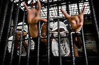 """Members of the Mara Salvatrucha gang (MS-13) show hand signs, representing their gang, in a cell at the detention center in San Salvador, El Salvador, 20 February 2014. Although the country's two major gangs reached a truce in 2012, the police holding cells currently house more than 3000 inmates, five times more than the official built capacity. Partly because the ordinary Mara gang members did not break with their criminal activities (extortion, street-level distribution of drugs, etc.), partly because Salvadorean police still applies controversial anti-gang law which allows to detain almost anyone for """"suspicion of gang membership"""". Accused young men are held in police detention centers where up to 25 inmates may share a cell of five-by-five metres. Here, in the dark overcrowded cages, under harsh and life-threatening conditions, suspected gang members wait long months, sometimes years, for trial or for to be transported to a regular prison."""