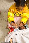 Preschool classroom girl in dressup firefighters jacket feeding doll pretend play vertical
