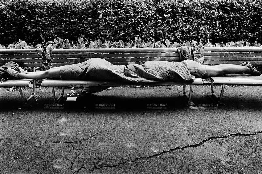 Switzerland. Zürich. A young couple is taking a nap on a bench. They both sleep under the same sleeping bag. Heads to heads, no faces, just feet. © 1990 Didier Ruef