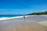 Boy with boogie board getting into water at Hapuna Beach, along the Big Island's Kohala Coast. This white sand beach has been rated one of the best beaches in the world time and time again.