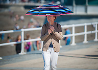 Aberystwyth, Ceredigion, West Wales, UK Monday 29th August 2016. UK Weather: People coming out and taking advantage of the fine Bank Holiday weather temperatures are expected to hit 19 degrees with clear skies. A woman walks on the prom and uses her umbrella as a sun shade.