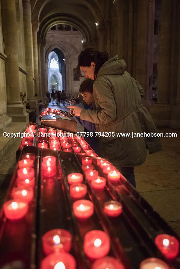 Lisbon, UK. 04.05.2015. People light candles within the Se de Lisboa (Lisbon Cathedral). Photograph © Jane Hobson.