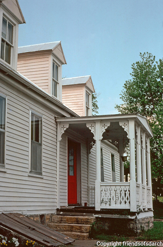 Augusta:  House with dormers.  Queen Anne ornamentation on porch.  Doors leading to basement.  Photo '77.