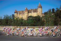 A pack of cyclists in the Tour de France pass a French castle. Culan, France.