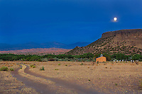 The moon rises behind the church at the base of Black Mesa a well known landmark in the San Ildefonso Pueblo in northern New Mexico.