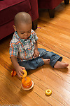 21 month old toddler boy sitting on floor playing with stacking ring toy