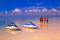 Two couples walk on a beach towards two jet skis.