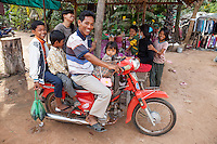 Cambodia.  Father and Children on a Motorbike, no Helmets.  Market near Siem Reap.