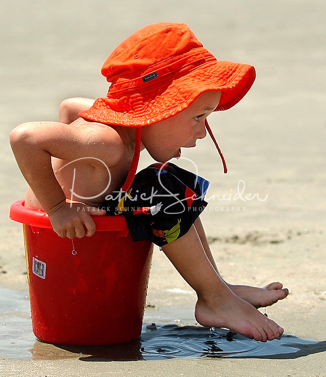 A young boy is stuck in a bucket while playing at the beach.