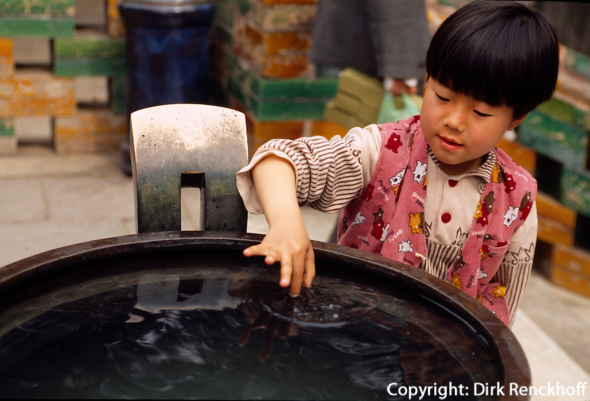 China, Tempel in der runden Stadt im Bei Hai-Park in Peking, Kind lässt Münze in Opferbecken schwimmen
