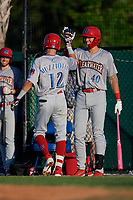 Clearwater Threshers Simon Muzziotti (12) high fives Alec Bohm (40) after hitting a home run during a Florida State League game against the Dunedin Blue Jays on May 11, 2019 at Jack Russell Memorial Stadium in Clearwater, Florida.  Clearwater defeated Dunedin 9-3.  (Mike Janes/Four Seam Images)