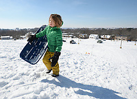 Murrell Craiglow, 7, of Fayetteville trudges back uphill with his sled Thursday, Feb. 18, 2021, while sledding near North Street and College Avenue in Fayetteville. Visit nwaonline.com/210219Daily/ for today's photo gallery. <br /> (NWA Democrat-Gazette/Andy Shupe)