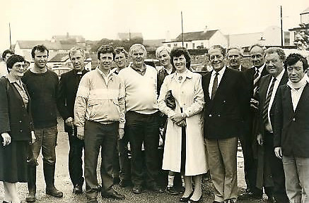 This group photo is of from the launch of currachs built by her dad Fechín in memory of his son Liam which were launched at Cleggan regatta in 1987, three years after Liam's death (from left to right) Teresa Murray, Thomas Madden, Fr John McCarthy, Thomas King, Peter A. Lacey, Seán Birmingham, William Hughes, Bernadette Conroy, Brian Lenihan Snr., Stephen King, Fechín Mulkerrin Snr., Mark Killilea and Séamus Brennan.