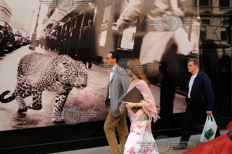 Couple passing advertsing for Chanel using image of a leopard, on Bond Street, London.