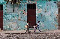 Antigua, Guatemala.  Mother and Two Children Walking, Poniente Street Scene.