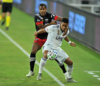 WASHINGTON, DC - SEPTEMBER 27: Brandon Bye #15 of New England Revolution battles for the ball with Ola Kamara #9 of D.C. United during a game between New England Revolution and D.C. United at Audi Field on September 27, 2020 in Washington, DC.