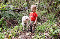 A young local boy with his dog pause along the native forest loop trail at Kalopa State Park, Hamakua Coast, Big Island.