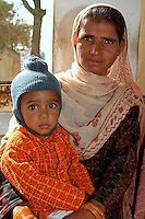 Portrait of mother and child waiting to be seen outside the medical clinic at Fort Dundlod, India.