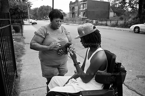Chicago, Illinois USA<br /> August  2011<br /> <br /> Ondelee Perteet  and his mother Deeteena  play with a puppy pit bull that Ondelee wants to buy.