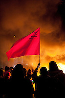 A protestor holds up a communist flag by fires on Parliament Square during a student demonstration in Westminster, central London on the day the government passed a bill to increase university tuition fees.