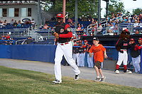 Batavia Muckdogs first baseman Javier Lopez (23) runs out to the field with a young fan before a game against the West Virginia Black Bears on June 29, 2016 at Dwyer Stadium in Batavia, New York.  West Virginia defeated Batavia 9-4.  (Mike Janes/Four Seam Images)
