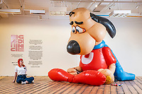 BNPS.co.uk (01202 558833)<br /> Pic: MaxWillcock/BNPS<br /> <br /> Pictured: GIANT gallery attendant Mise Maher sat beside 'Underdog', a giant, inflatable cartoon dog in a superhero costume created by American artist Chad Person this year, at the GIANT gallery in Bournemouth.<br /> <br /> 'Big Medicine', an exhibition celebrating our connection with one another in public space, is the inaugural display in GIANT, a new 15,000 square foot gallery in a former Debenhams in Bournemouth.
